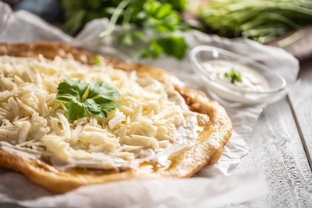 Крупный план запеченных венгерских ланго, которые подают со сливками, сыром, чесноком и свежим зеленым луком.