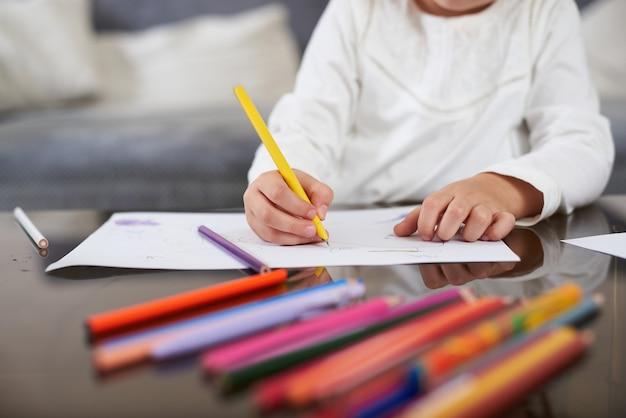 Крупный план маленькой детской руки, держащей желтую ручку и что-то писать на бумаге. цветные карандаши на переднем плане.