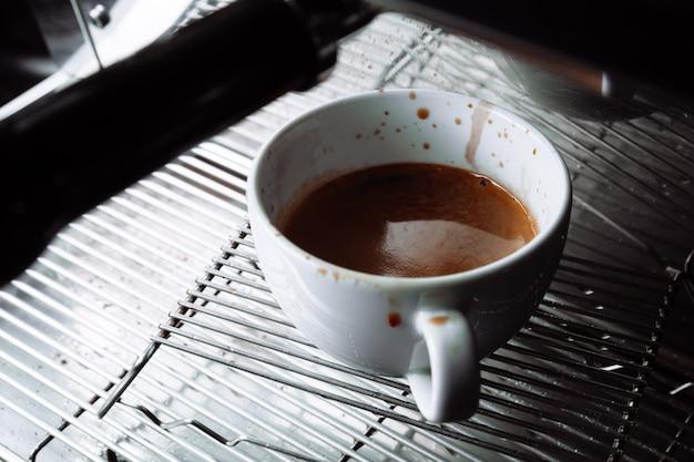 Крупный план машины, разливающей кофе в чашку, на чашке капли кофе