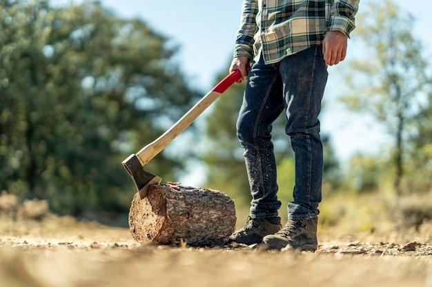 斧で木の幹を切る男性のクローズアップ