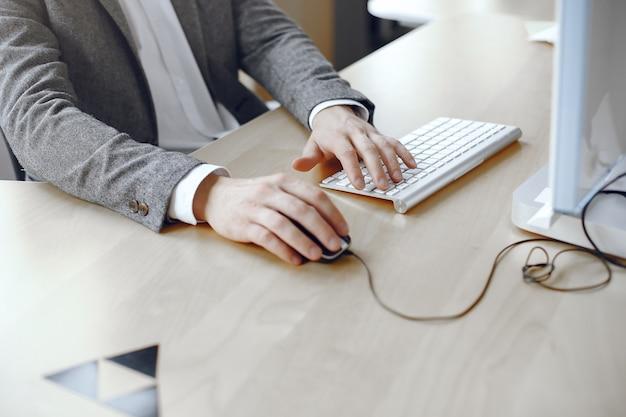 Крупным планом мужские руки заняты набором текста на ноутбуке. мужчина в офисе.