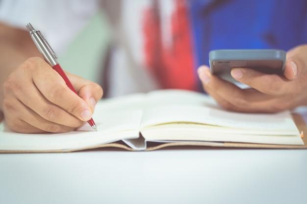 Крупным планом студент мужского пола делает заметки во время урока на смартфоне дома