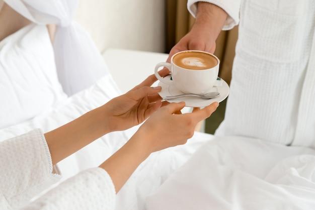 Крупным планом мужчина приносит кофе своей подруге, лежащей в постели