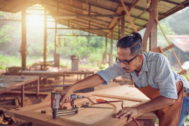 Крупный план плотника человека, использующего пистолет для гвоздя. плотник, использующий пневматический пистолет для гвоздя, делает работу с деревянной мебелью, винтажный стиль