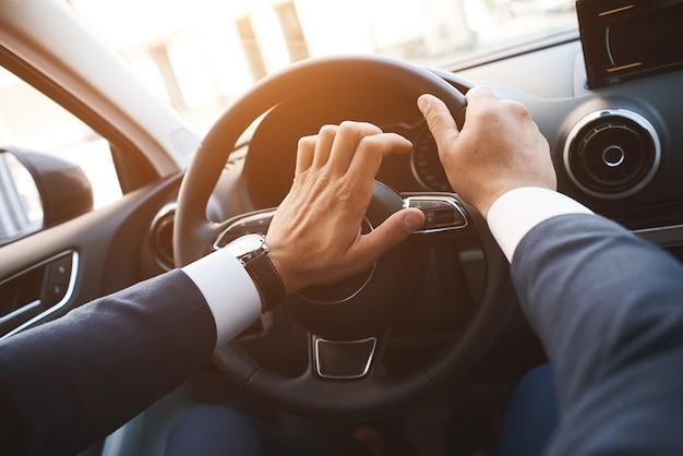 ホーンボタンの夕日に手で車を運転する男のクローズアップ