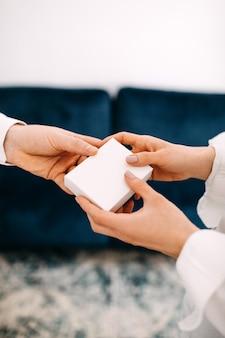 女性にギフトボックスを与える男性のクローズアップ手に白い空白のボックス