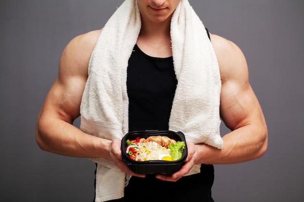 Крупный план человека, держащего коробку, полную белков богатых продуктов для спортивного питания