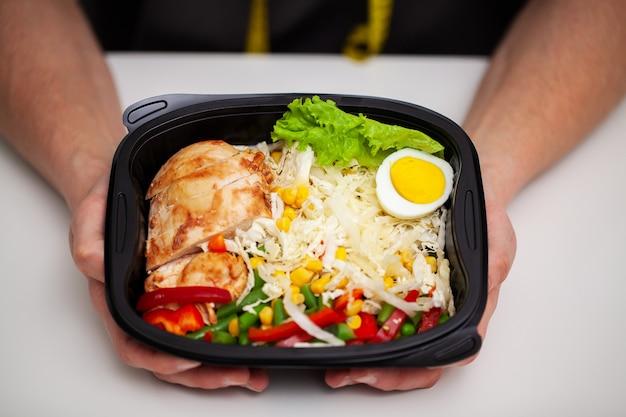 스포츠 영양을위한 단백질이 풍부한 음식으로 가득한 상자를 들고 남자의 근접 촬영