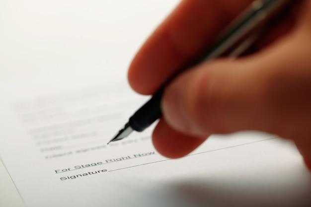 문서를 수행하는 동안 펜을 들고 남자의 근접 촬영. 필드의 얕은 깊이로 촬영.