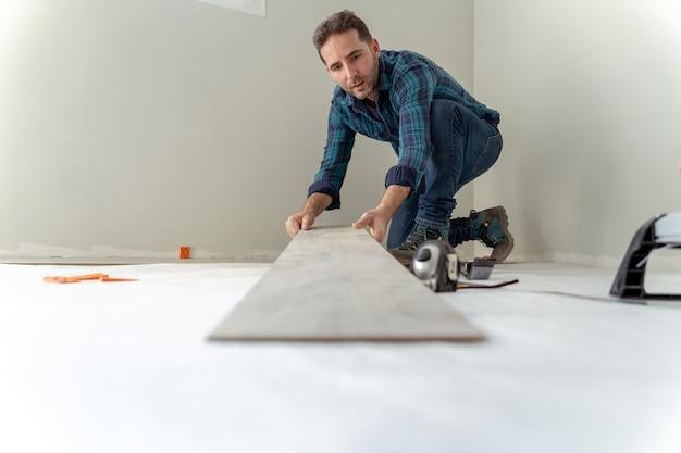 집 바닥을 설치하기 위해 나무 한 장을 들고 남자의 근접 촬영