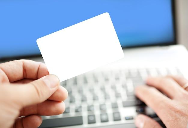 신용 카드로 노트북을 사용 하여 온라인 쇼핑하는 남자의 근접 촬영. 신용 카드가 비어 있습니다. 신용 카드 템플릿