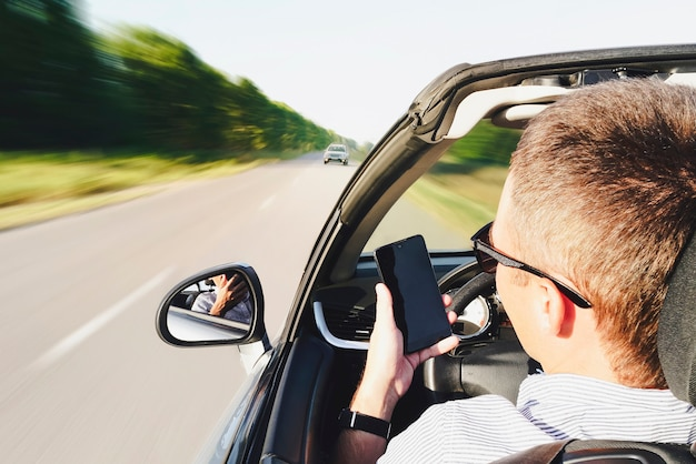 차를 운전하는 동안 스마트폰을 사용하는 남자의 근접 촬영. 마주 오는 차량으로 운전. 위험한 움직임. 전화로 주의가 산만합니다. 그 남자는 운전 중에 전화로 메시지를 씁니다. 효과 흐릿한 동작
