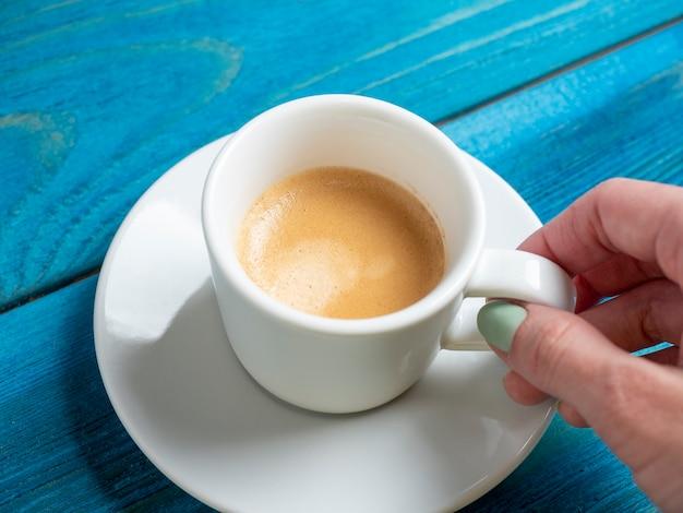 白い受け皿の上に芳香族エスプレッソの小さな白いカップを持っている男の手のクローズアップ