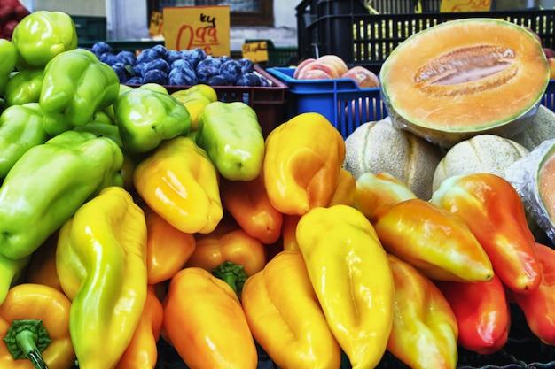 백그라운드에서 파프리카, 노란색 멜론 또는 통통과 같은 야채를 판매하는 마을의 시장을 닫습니다.