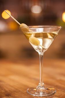 레스토랑에서 나무 테이블에 올리브와 마티니 유리의 근접 촬영. 신선한 음료입니다. 맛있는 음료. 알코올 음료.