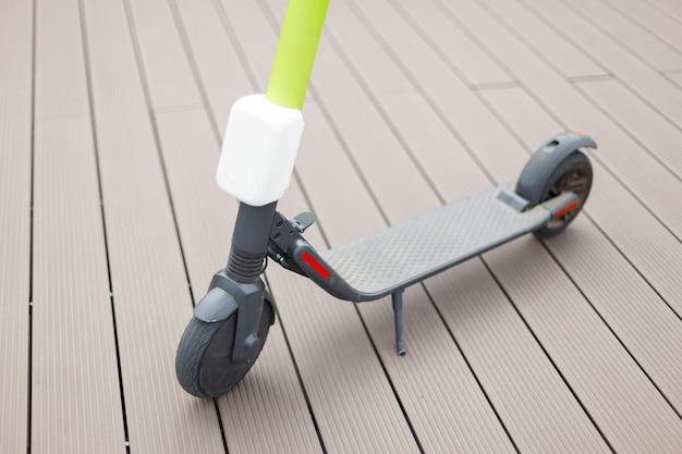 木製の床にモダンな電動スクーターのクローズアップ。現代の生態学的輸送。詳細。
