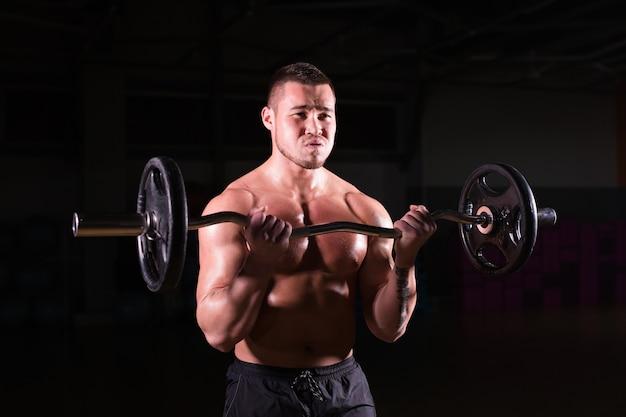 暗い壁にウェイトを持ち上げる筋肉の若い男のクローズアップ