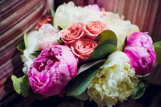 분홍색과 보라색 꽃과 음소거 웨딩 부케의 근접 촬영.
