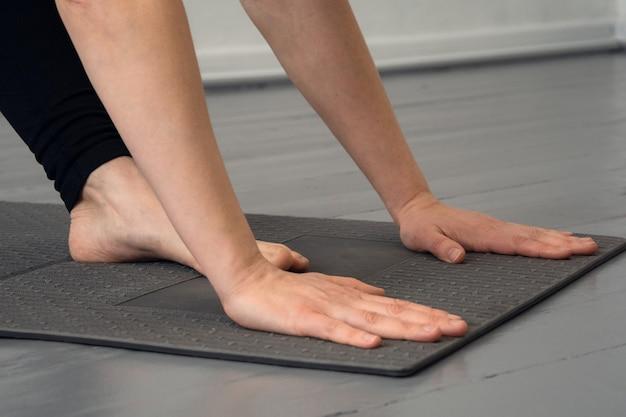 Крупным планом человека, занимающегося йогой или фитнесом на черном коврике