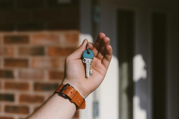 Крупным планом лицо руки, держащей ключи с размытым фоном