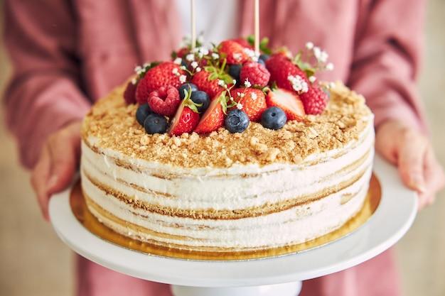 과일과 크림 같은 맛있는 케이크를 들고 있는 사람의 클로즈업