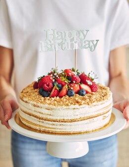 「お誕生日おめでとう」トッパーでフルーティーなケーキを持っている人のクローズアップ