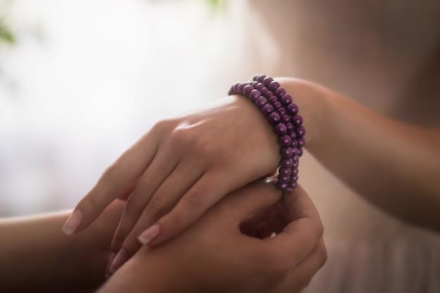 ライトの下で女性の手の周りに紫色のブレスレットを置く人のクローズアップ