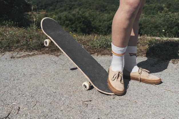 ぼやけた日光の下で公園でスケートボードをしている人のクローズアップ