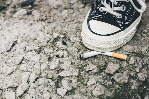 Крупный план ноги человека в черных кроссовках. ботинки давят окурком на асфальте. концепция отказа от курения