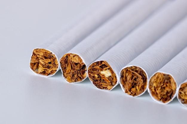 Крупным планом куча сигарет на белом фоне