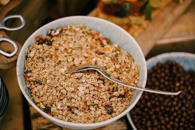 Крупный план тарелки овсянки с сухофруктами на столе с шариками из хлопьев для завтрака с какао