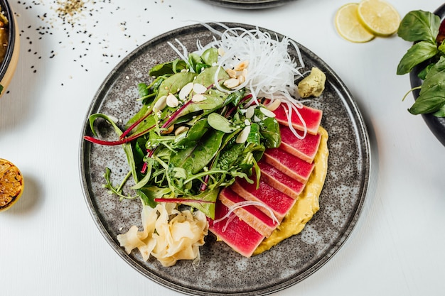 白いテーブルの上の新鮮な野菜と寿司のプレートのクローズ アップ