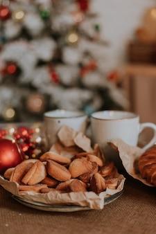 Крупным планом тарелка с выпечкой и сладостями и белые кружки на столе в рождественской кухне