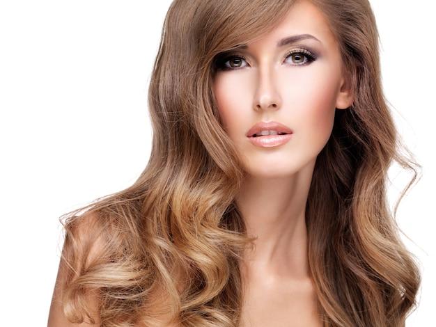 美しい長い茶色の髪のポーズできれいな女性のクローズアップ。白で隔離