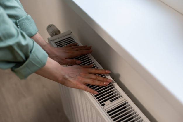 Крупным планом термостат радиатора с рукой женщины