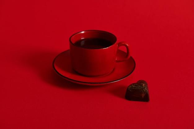 受け皿に赤いセラミックカップのコーヒーとハート型のチョコレートプラリネのクローズアップ。テキストのためのスペースと赤い表面のチョコレートの日の概念