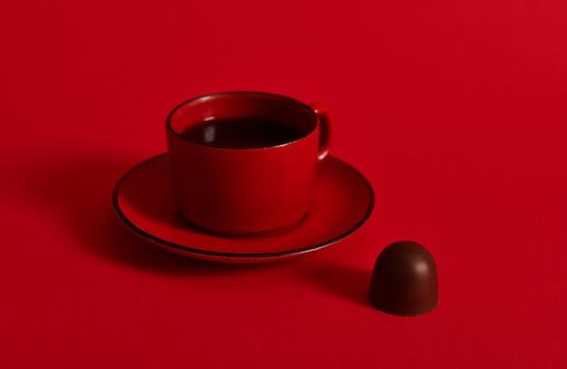 受け皿の上の赤いセラミックカップのコーヒーとコピースペースのある赤い表面のチョコレートプラリネのクローズアップ。チョコレートデーのコンセプト