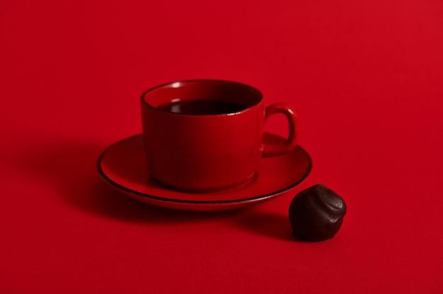 受け皿に赤いセラミックカップのコーヒーと赤い表面にチョコレートトリュフのクローズアップ。