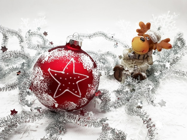 Крупным планом красный рождественский орнамент с гирляндами на белой поверхности