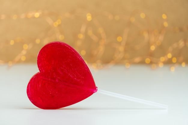 Крупным планом леденец на палочке в форме красного сердца с размытым фоном