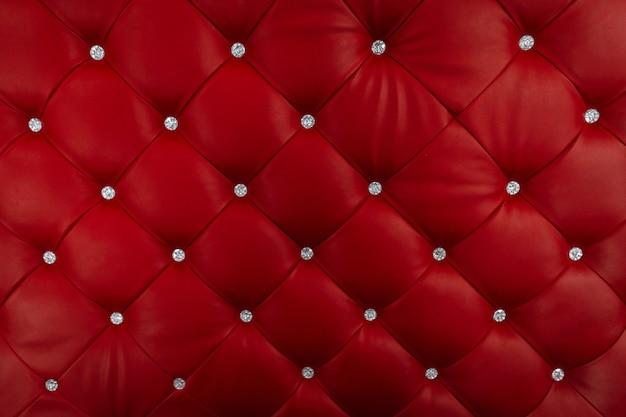 반짝이는 버튼으로 장식 된 빨간 가죽 소파의 근접 촬영