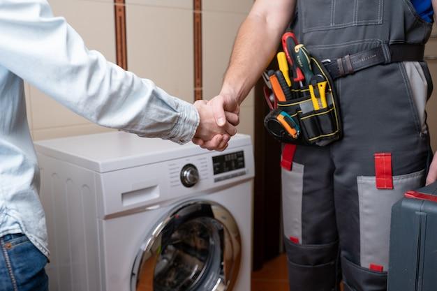 洗濯機の修理のための女性の顧客男性の修理工と握手する修理工のクローズアップ