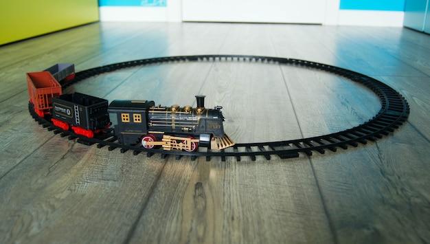 カラフルな子供部屋の床にある円形のトラックにレトロなおもちゃの列車のクローズアップ