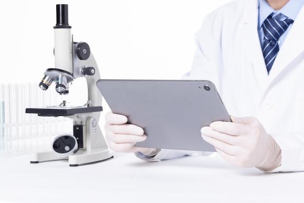 연구 결과를 분석하기 위해 실험실에서 태블릿을 사용하는 과학자의 근접 촬영