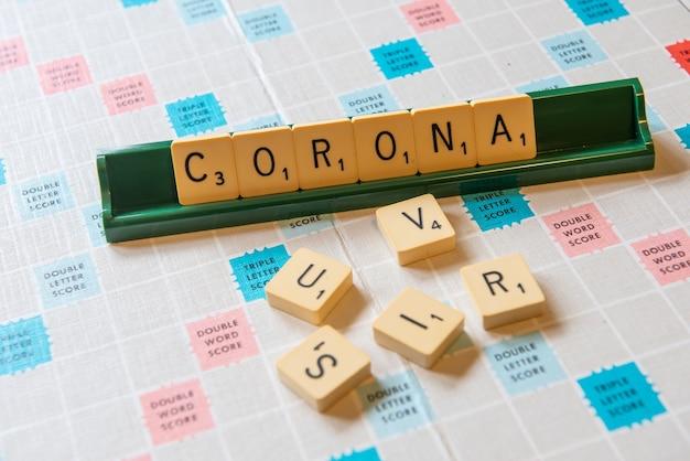 조명 아래에 코로나와 바이러스라는 단어가있는 스크램블 보드의 근접 촬영