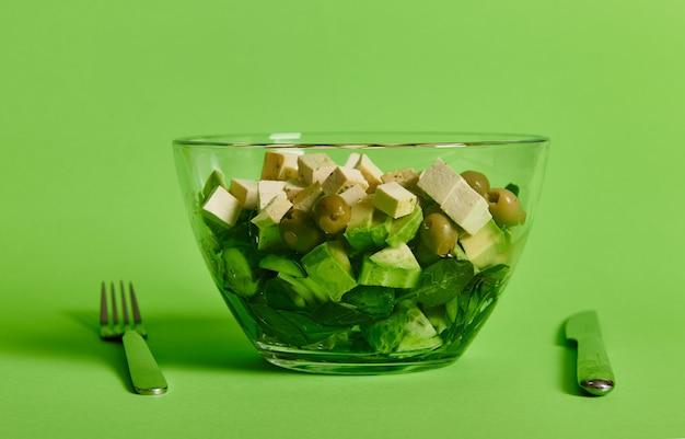 Крупный план сервировочной миски с зеленым салатом и овощами и веганским сыром тофу