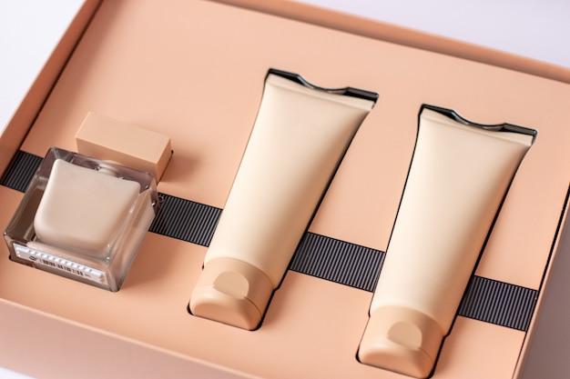 Крупным планом набор парфюмированного геля для душа кремового цвета в подарочной коробке