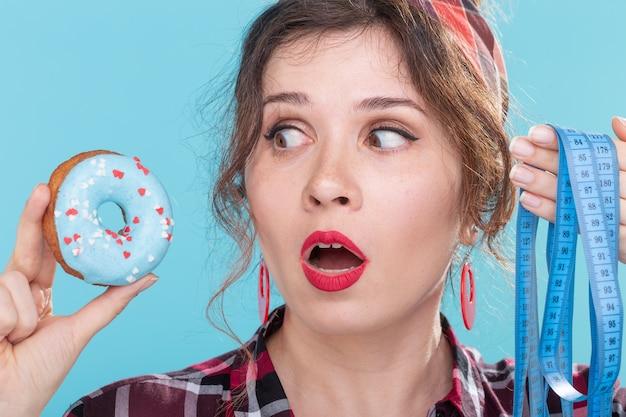 그녀의 손에 파란색 도넛을 들고 측정 충격과 화가 젊은 아름 다운 여자의 근접 촬영