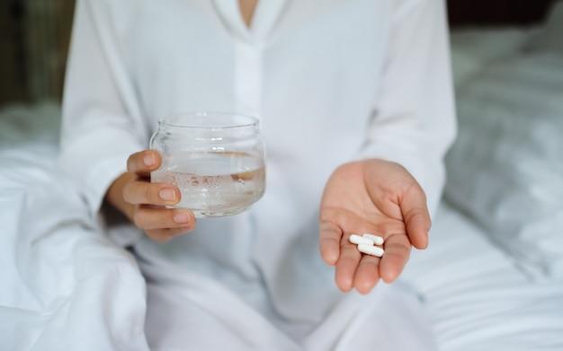 Крупным планом больной женщины, держащей белые таблетки и стакан воды, сидя на кровати