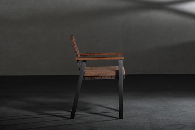 회색 벽이있는 방에 금속 다리가있는 간단한 현대 의자의 근접 촬영